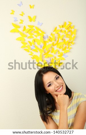 Girl near paper butterflies fly on wall - stock photo