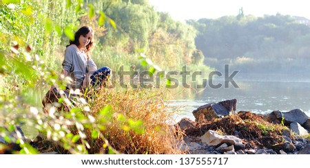 Girl near the river at sunset - stock photo