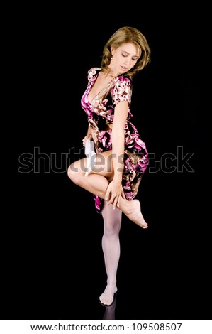 Girl-next-door beauty in colorful spring outfit removing her stocking seductively. - stock photo