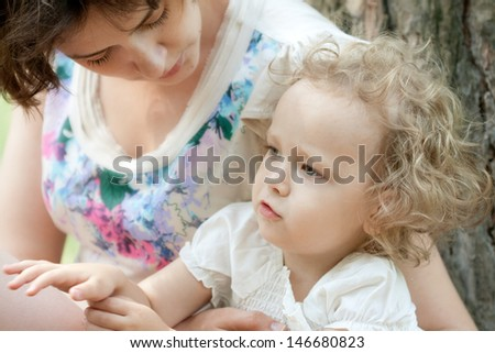 Girl of three years with her mother outdoors - stock photo