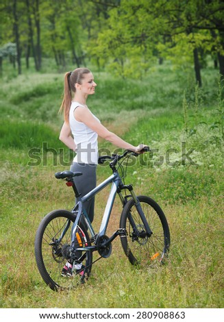 Girl on a bicycle in a forest  - stock photo