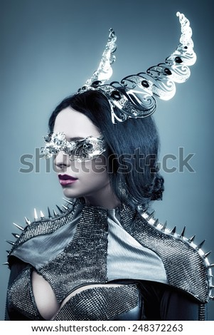 girl on a blue background with decorations on the head   - stock photo