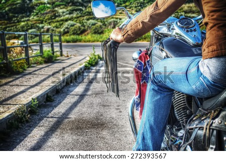 girl on a classic motorcycle on the edge of the road in hdr - stock photo