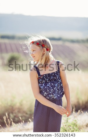 Girl on a field with a flower garland on a summer day - stock photo