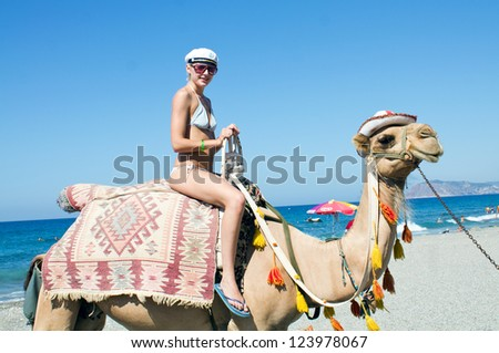 Girl on a funny camel. - stock photo