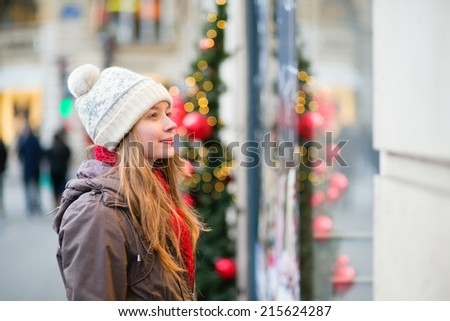 Girl on a Parisian street looking at shop windows decorated for Christmas - stock photo