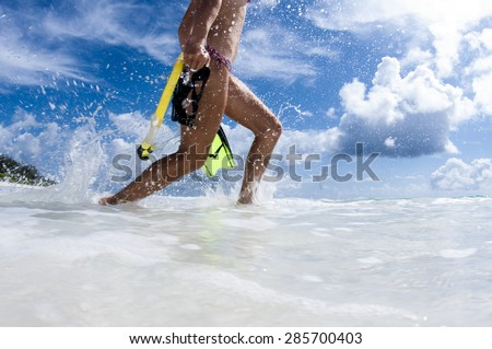 Girl on beach running into ocean to go snorkelling - stock photo