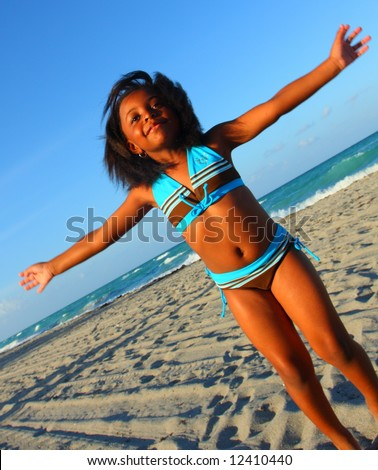Girl on beach with arms extended - stock photo