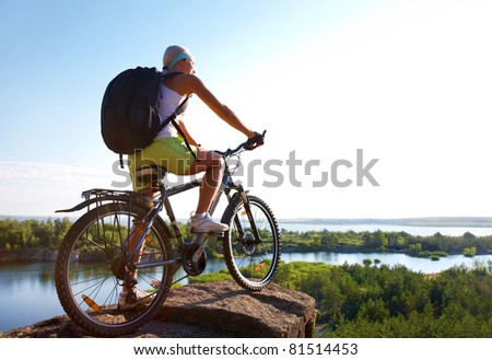 Girl on bike stands high on a hill and looks forward to the natural open spaces - stock photo