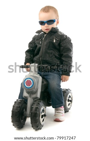 Girl on child's motorcycle in leather jacket and with glasses, on whites background. - stock photo