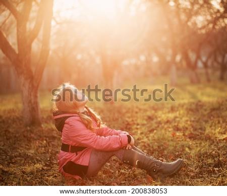 girl on grass in autumn garden - stock photo