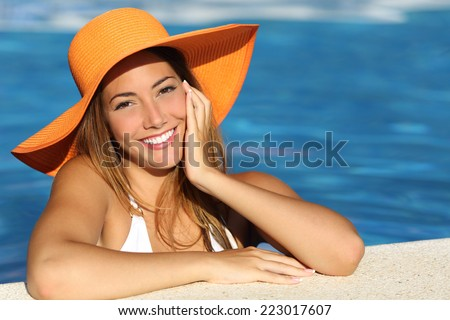 Girl on holidays with a perfect white smile bathing in a pool on vacations - stock photo