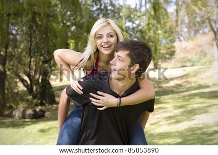 Girl on piggyback of boy friend in green park with trees - stock photo