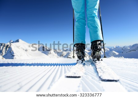 Girl on ski standing on the fresh snow on newly groomed ski piste at sunny day in mountains - stock photo