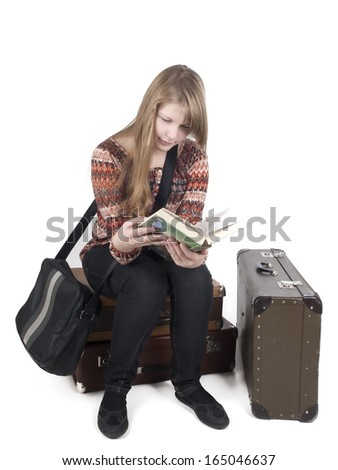 girl on suitcases with books on a white background in studio - stock photo