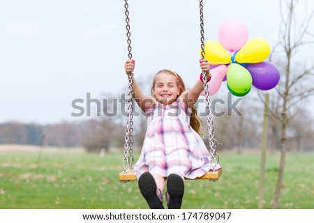 girl on swing with air balloons smiling - stock photo
