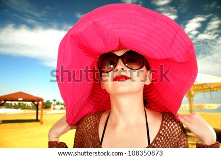 girl on the beach in a red hat, a large glasses summer - stock photo
