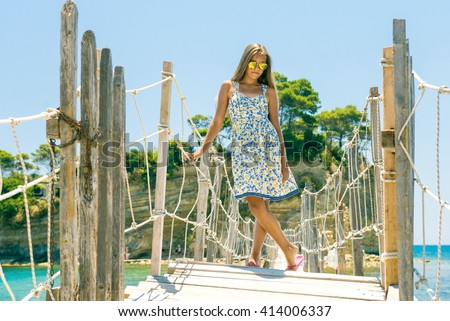 Girl on the bridge. Happy teen girl with long hair in the summer,  girl bent over the railing, girl in sunglasses outdoors - stock photo