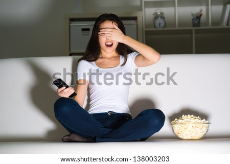 girl on the couch closed my eyes, watching horror movies at night - stock photo