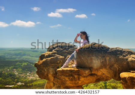 Girl on the edge of a mountain looking at the landscape - stock photo