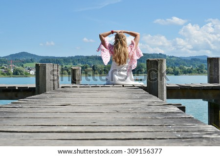 Girl on the wooden jetty at the  lake. Switzerland - stock photo