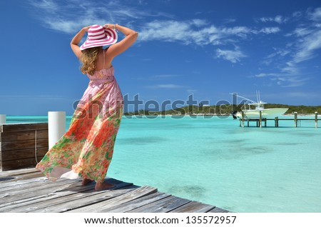 Girl on the wooden jetty looking to the ocean. Exuma, Bahamas - stock photo