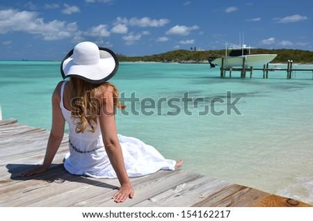 Girl on the wooden jetty looking to the ocean. Exuma, Bahamas - stock photo