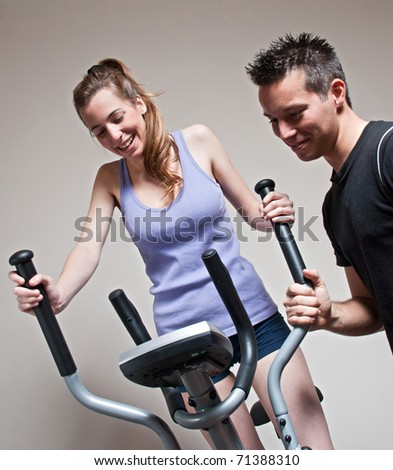 Girl on training apparatus and instructor in sportclub - stock photo