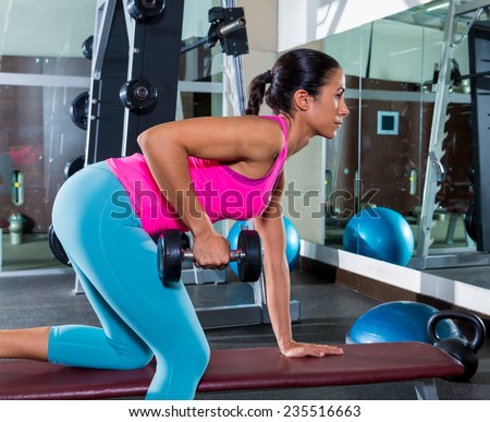 girl one arm dumbbell bent over row on bench workout exercise at gym - stock photo