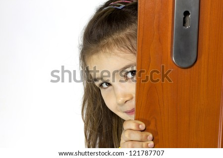 Girl opening the door and mysterious smiling - stock photo