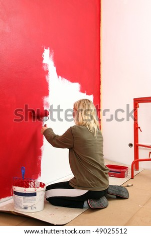 Girl painting living room in a red color. - stock photo