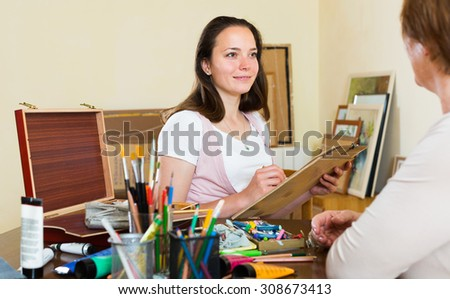Girl painting  portrait of mature woman at workshop - stock photo