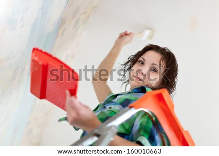 girl paints ceiling with brush at home - stock photo