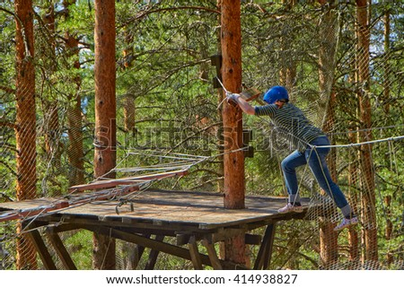 Girl passing through obstacles in a Forest Rope Park Challenge - stock photo