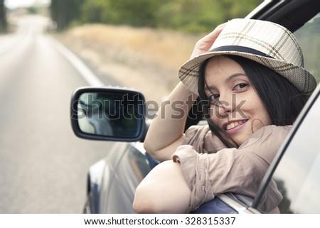 girl peeking through the car window - stock photo