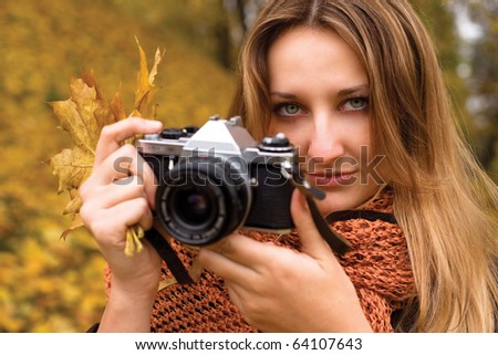 Girl photographer making pictures of autumn forest - stock photo