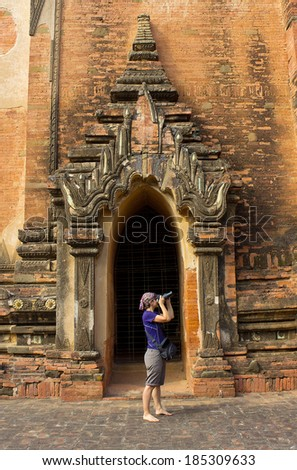 girl photographer take a picture in arch of the temple in Bagan(Pagan), Myanmar(Burma), november 2014 - stock photo