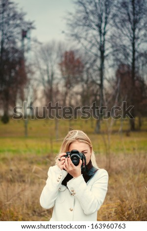 Girl photographer with camera outdoors at the park - stock photo