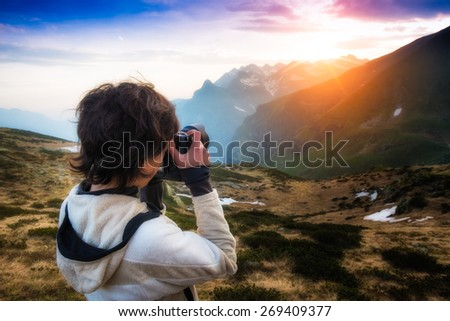 Girl photographing the sunset in the mountains - stock photo