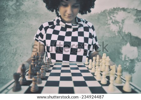 Girl playing a game of chess.  - stock photo