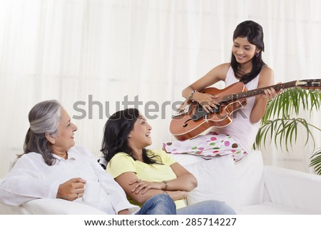 Girl playing guitar for her mother and grandmother - stock photo