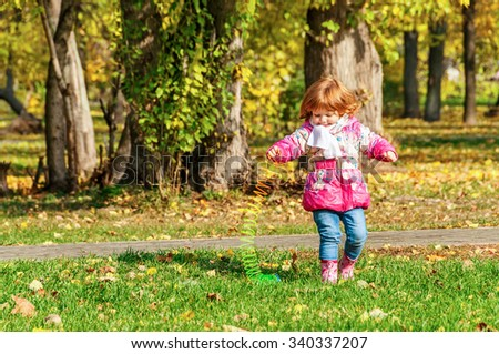 Girl playing in the park with a Rainbow spiral spring  - stock photo