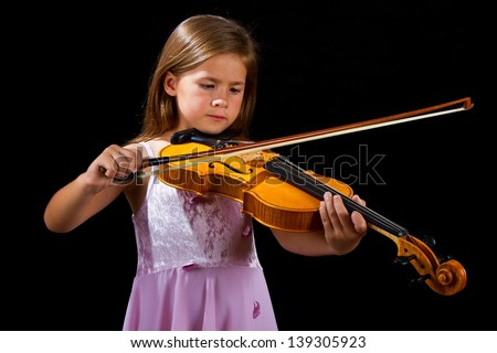 Girl playing violin in pink dress concentration on black - stock photo
