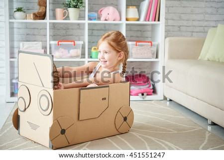 Girl playing with car made of cardboard box - stock photo