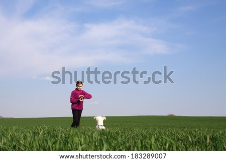Girl playing with her dog on the grass - stock photo