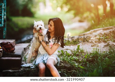 girl playing with her dog somewhere in the park - stock photo
