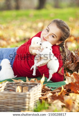 Girl playing with her five puppies in the park - stock photo