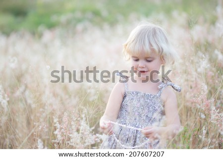 Girl playing with her necklace in a field - stock photo