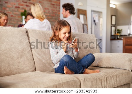 Girl playing with new technology while adults entertain - stock photo