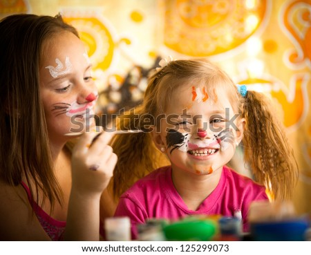 Girl playing with painting with sister - stock photo